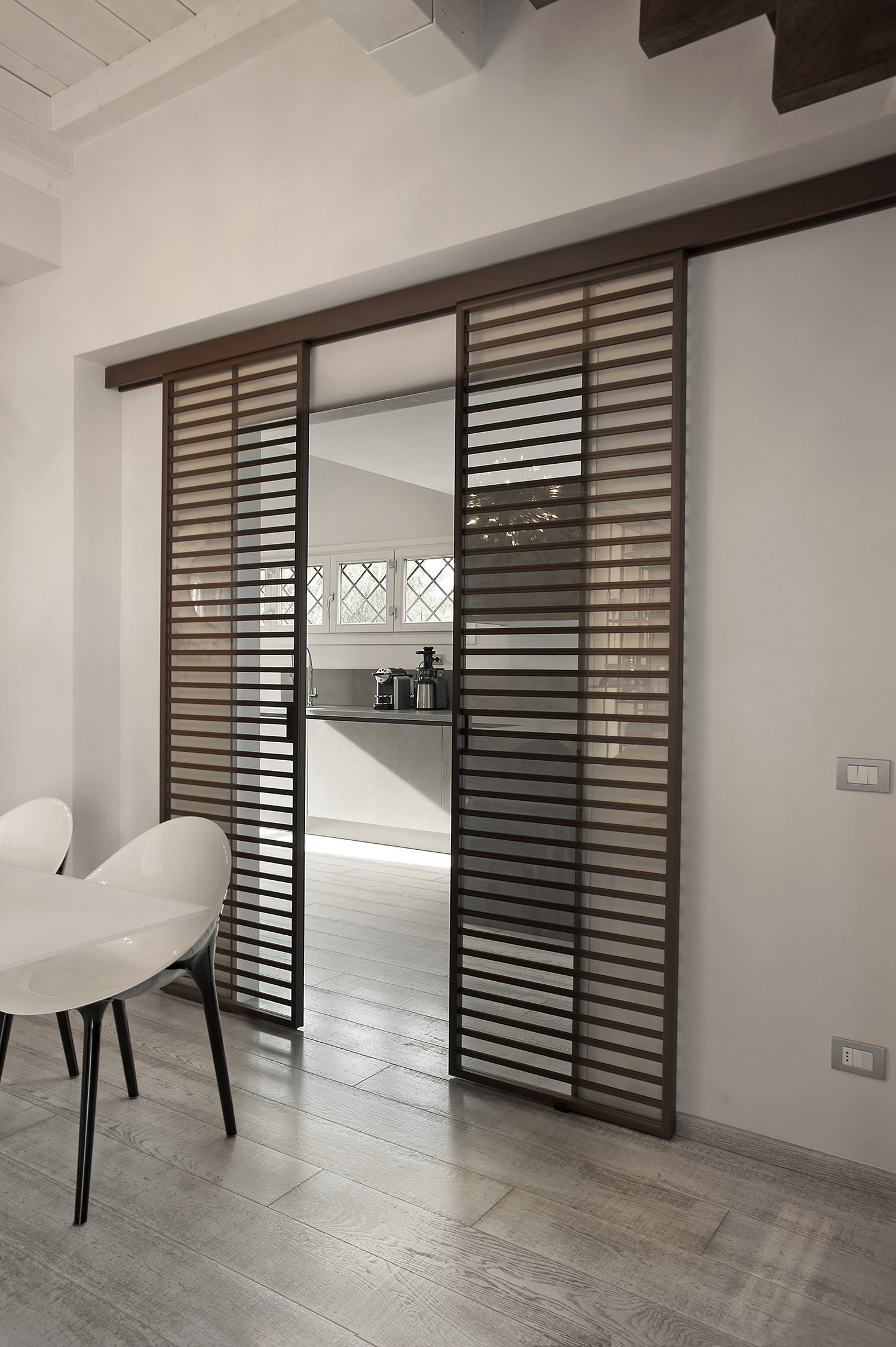 access to the bedroom area is given through a sliding system made of a hollow core door leaf from the segreta collection the door is covered in walnut